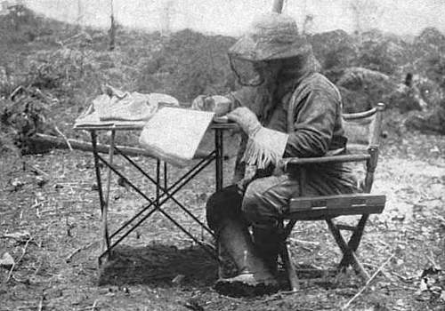 Photo of Theodore Roosevelt, while on expedition, outdoors in South America seated at a table making notes.