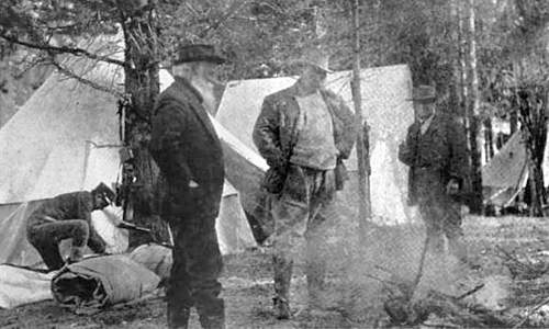 Photo of John Burroughs and Theodore Roosevelt standing in a camp with tents in the background