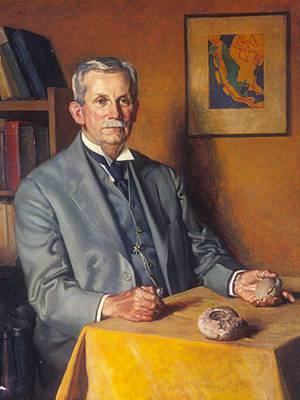 Portrait of Charles Schuchert sitting at small table holding a fossil