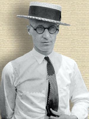 Photo of John Scopes, upper body facing forward, wearing straw hat, shirt and tie, outdoors