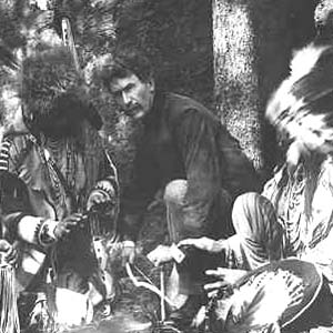 Photo of Ernest Thompson Seton with Blackfoot Indians, starting a fire with bow and stick