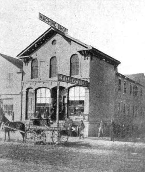 Photo: Front street view of 2 story building with basement. Horse wagon in front. Signs