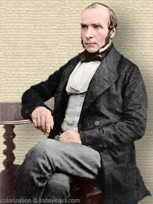 Photo of John Snow, full body seated, legs crossed, arm on side table, facing mid-left. Colorization © todayinsci.com