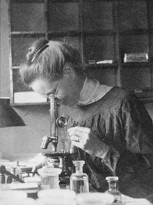 Photo of Nettie Stevens looking into a microscope on a laboratory bench with glass bottles, basins