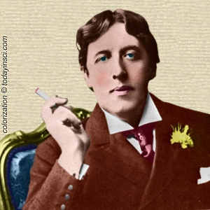 Photo of Oscar Wilde, seated, face forward, cigarette in raised right hand. Colorization © todayinsci.com