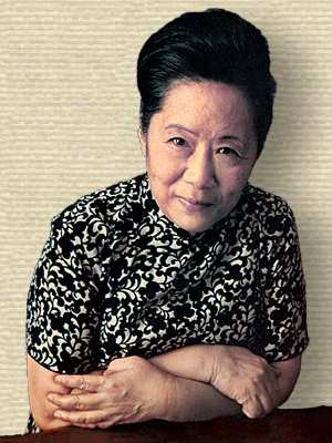 Photo of Chien-Shiung Wu, upper body, facing forward, arms folded leaning on table top.