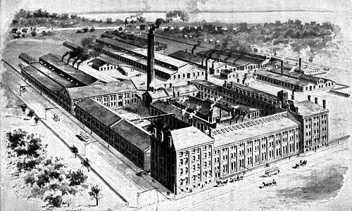Drawing of Yale & Towne plant: Multi-story buildings covering about two city blocks. Electric trolleys run on bordering streets.