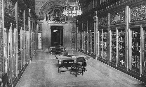 Photo of interior of Yale showroom, showing tall glass wall display cabinets in an elegantly decorated room with a chandelier