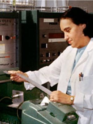 Photo of Rosalyn Yalow standing in front of lab electronic analysis equipment, upper body, facing left, in lab coat